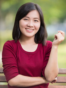 asian woman sitting on park bench