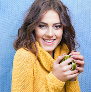 beautiful natural young smiling brunette woman wearing knitted sweater drinking cup of coffee